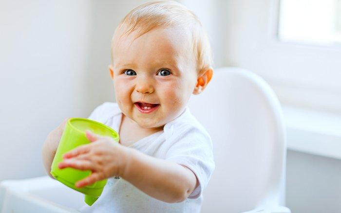 ребенок пьет из чашки
