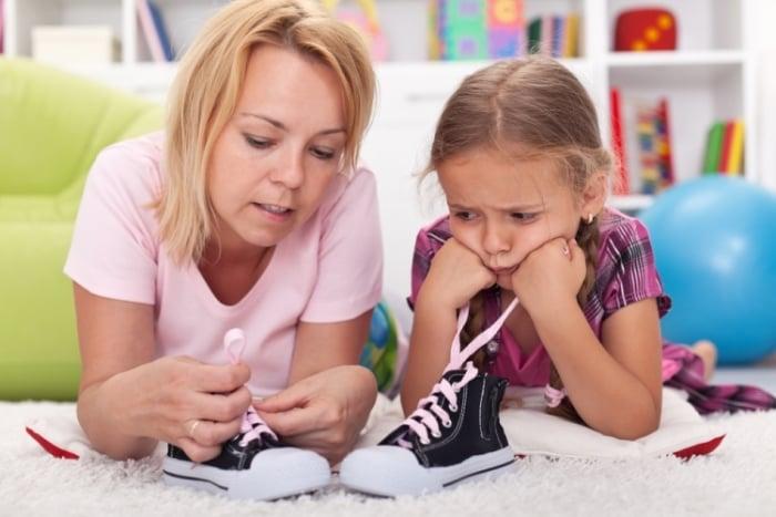 мама учит ребенка завязывать шнурки