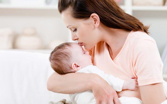 мама укладывает ребенка в кроватку