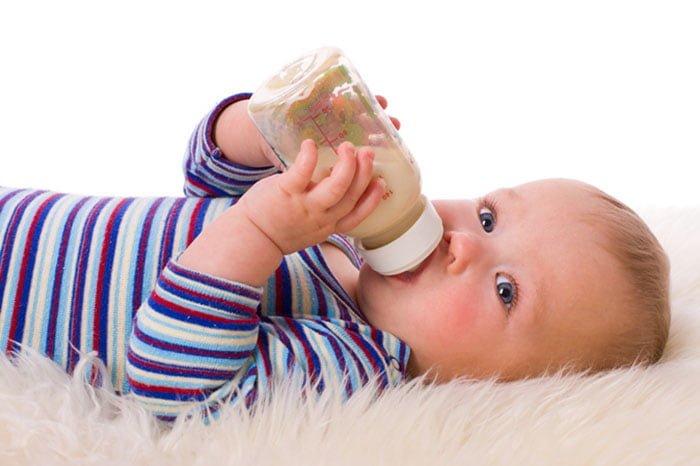 малыш пьет лекарство из бутылочки