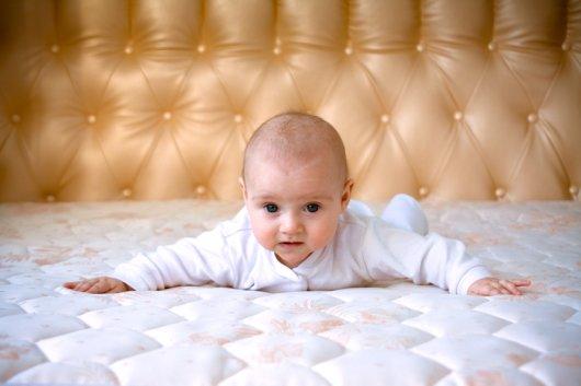 малыш лежит на матрасе