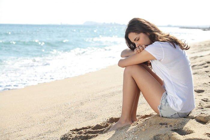 девушка сидит на берегу моря