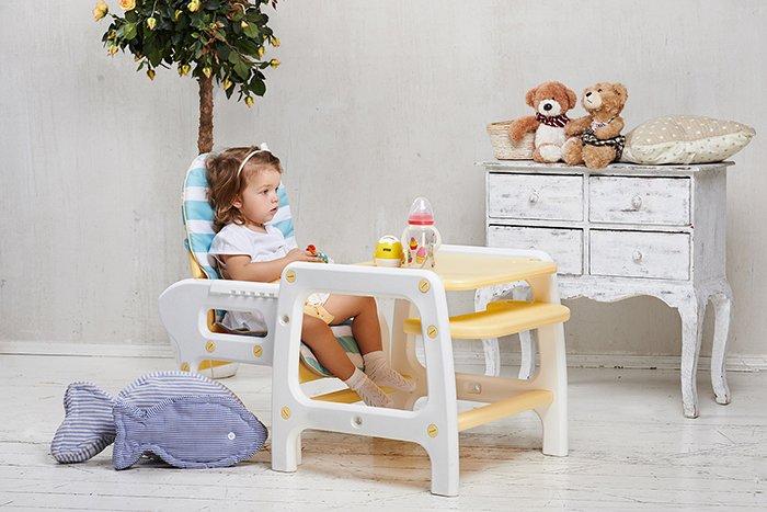 девочка сидит на стуле для кормления