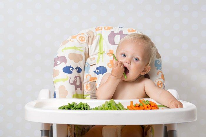 малыш сидит на стульчике для кормления