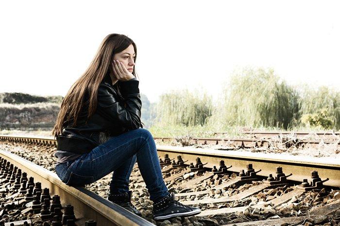 девушка сидит на железной дороге
