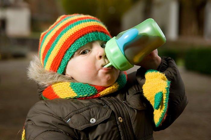 ребенок пьет из поильника