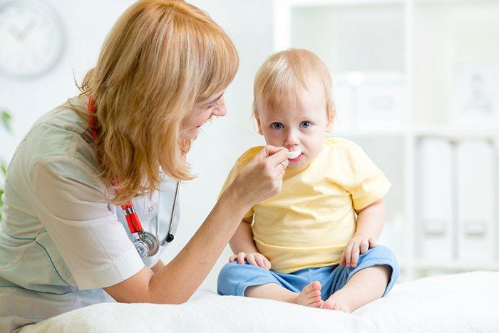 врач дает сироп ребенку