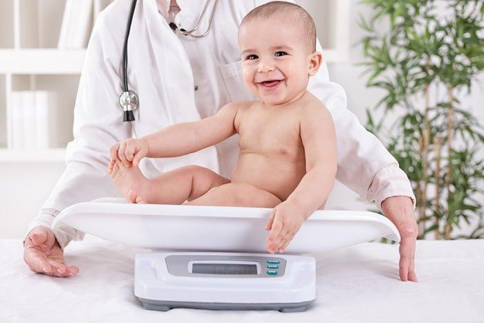 врач взвешивает ребенка на весах