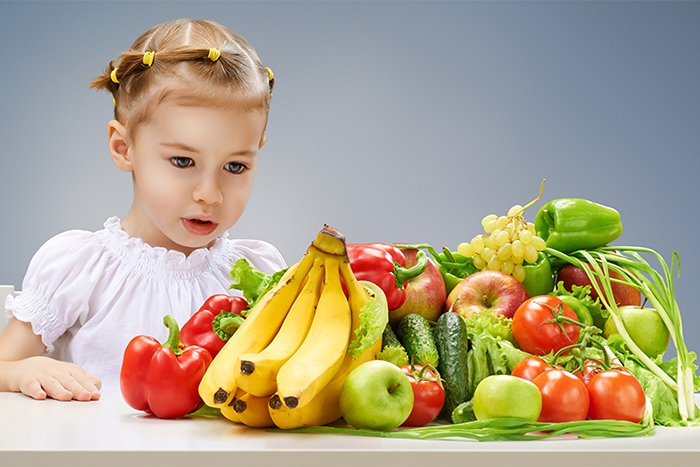 девочка за столом с овощами и фруктами