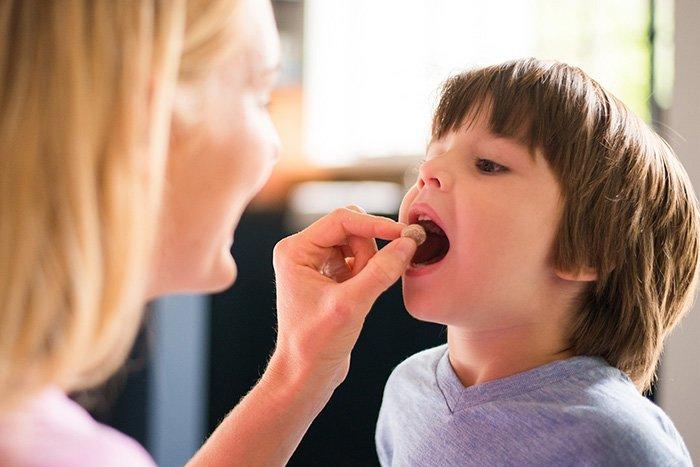 мать дает ребенку витамины