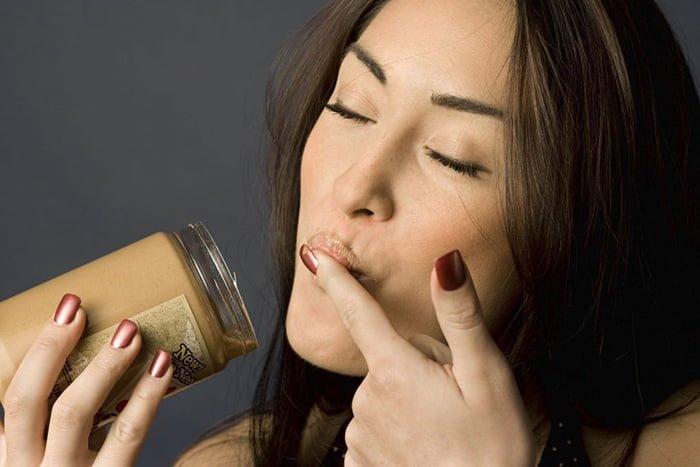 девушка ест арахисовую пасту