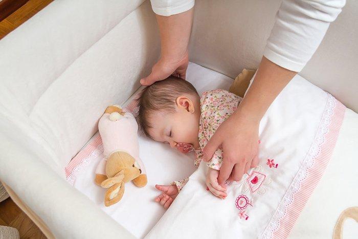 мама уложила ребенка в кровать