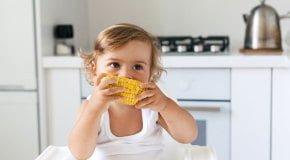 Ребенок ест кукурузу вареную