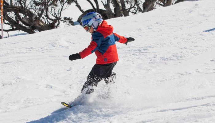 Ребенок учится кататься на сноуборде