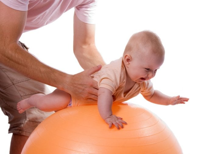 малыш тянется за игрушкой на фитболе