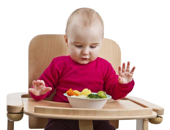 маленький ребенок ест овощи