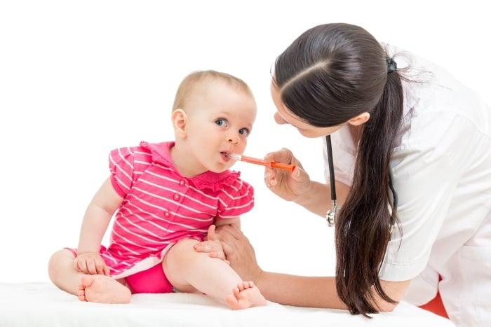 врач вводит линекс в рот малыша