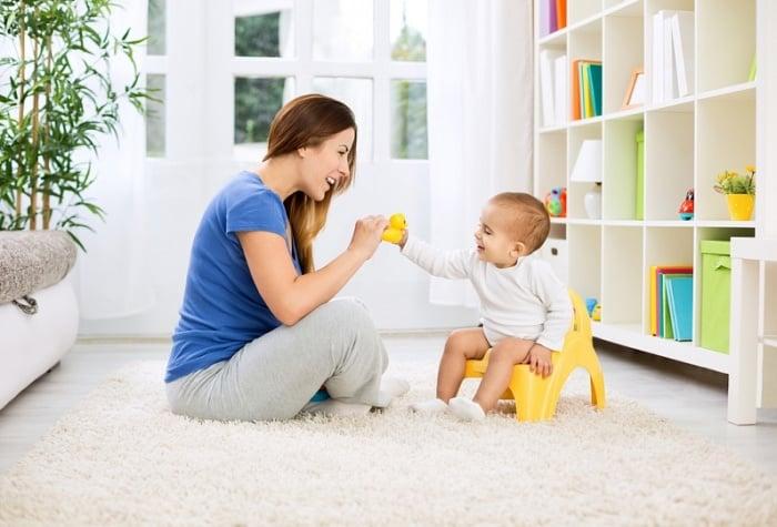 мама смотрит как ребенок сидит на горшке