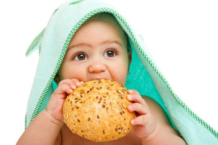 малыш ест булочку