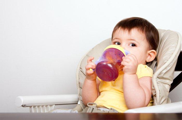 малыш пьет напиток из бутылочки