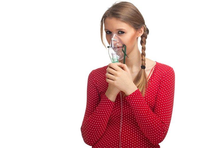девушка дышит в ингалятор