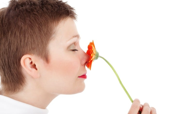 девушка нюхает запах цветка