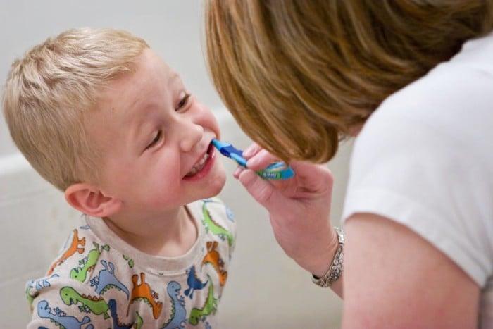 мама показывает ребенку, как чистить зубы