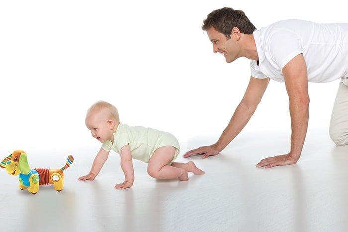 папа учит малыша ползать