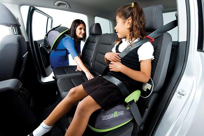 школьница сидит на бустере в машине