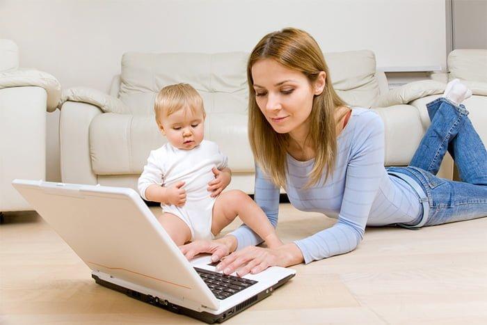 мама с грудничком за ноутбуком