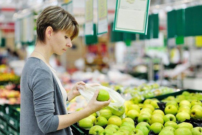 девушка выбирает яблоки