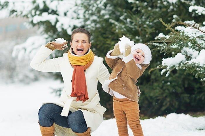 мама и ребенок играют со снегом