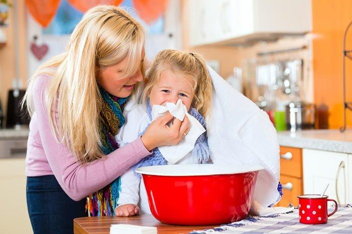 мама помогает ребенку высмаркиваться