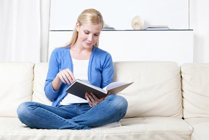 девушка читает книгу на диване