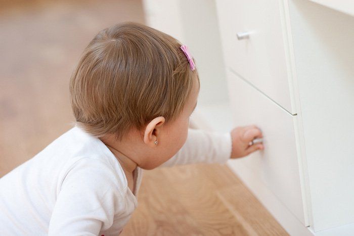 ребенок пытается открыть ящик