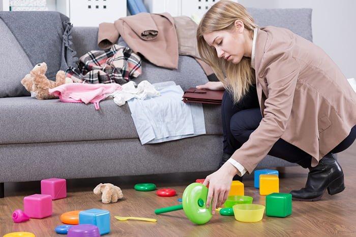 мама убирает игрушки за ребенка