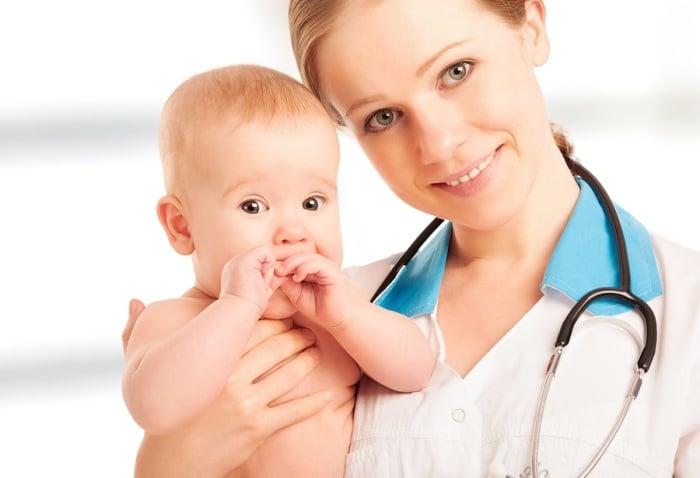 Девушка врач держит ребенка