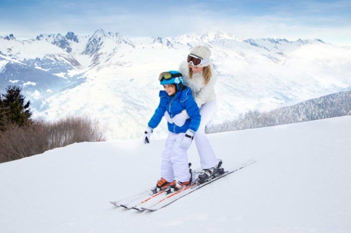 Мама и ребенок катаются на лыжах вместе